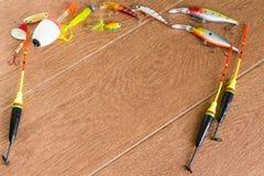 Aparejos de pesca del capítulo - giro, ganchos y señuelos de la pesca en fondo de madera ligero Visión superior Fotografía de archivo libre de regalías