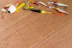 Aparejos de pesca del capítulo - giro, ganchos y señuelos de la pesca en fondo de madera ligero Visión superior Imagenes de archivo
