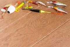Aparejos de pesca del capítulo - giro, ganchos y señuelos de la pesca en fondo de madera ligero Visión superior Imagen de archivo libre de regalías