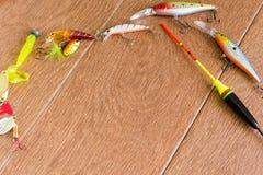 Aparejos de pesca del capítulo - giro, ganchos y señuelos de la pesca en fondo de madera ligero Visión superior fotos de archivo libres de regalías
