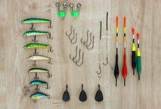 Aparejos de pesca - pesca del flotador, de señuelos, de pesos y de campanas en fondo de madera hermoso imagenes de archivo