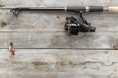 Aparejos de pesca - del giro, de los ganchos y de señuelos de la pesca en viejo fondo de madera imagen de archivo libre de regalías