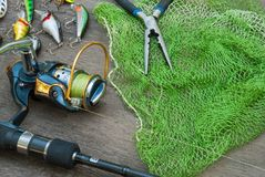 Aparejos de pesca - el giro, los ganchos y los señuelos de la pesca encendido oscurecen el fondo de madera fotografía de archivo