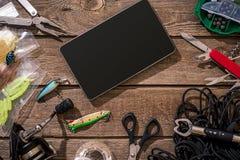 Aparejos de pesca - giro de la pesca, línea, ganchos y señuelos en fondo de madera Fotos de archivo