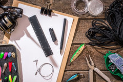 Aparejos de pesca - giro de la pesca, línea, ganchos y señuelos en fondo de madera Foto de archivo