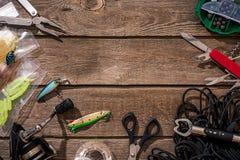 Aparejos de pesca - giro de la pesca, línea, ganchos y señuelos en fondo de madera Imagen de archivo libre de regalías
