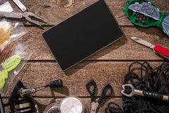 Aparejos de pesca - giro de la pesca, línea, ganchos y señuelos en fondo de madera Imagenes de archivo