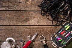 Aparejos de pesca - giro de la pesca, línea, ganchos y señuelos en fondo de madera Foto de archivo libre de regalías