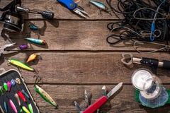 Aparejos de pesca - giro de la pesca, línea, ganchos y señuelos en fondo de madera Imagen de archivo