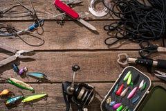 Aparejos de pesca - giro de la pesca, línea, ganchos y señuelos en fondo de madera Imágenes de archivo libres de regalías