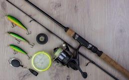 Aparejos de pesca - giro, ganchos y señuelos de la pesca en fondo de madera ligero foto de archivo