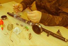 Aparejos de pesca - giro, ganchos y señuelos de la pesca en fondo de madera ligero fotos de archivo