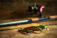 Aparejos de pesca - giro, ganchos y señuelos de la pesca en fondo de madera ligero Visión superior Fotografía de archivo libre de regalías