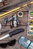 Aparejos de pesca para el viaje en los tableros de madera Foto de archivo libre de regalías