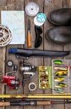 Aparejos de pesca para el viaje en los tableros de madera Imágenes de archivo libres de regalías