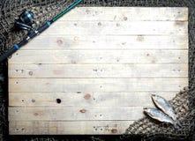 Aparejos de pesca y aún-vida secada de los pescados en el backgroun de madera Fotografía de archivo libre de regalías