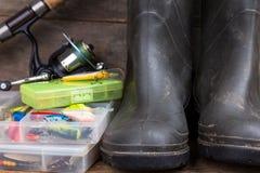 Aparejos de pesca y botas de goma en tablero de la madera Imágenes de archivo libres de regalías