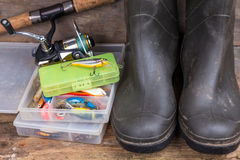 Aparejos de pesca y botas de goma en tablero de la madera Fotos de archivo