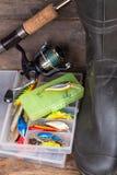 Aparejos de pesca y botas de goma en tablero de la madera Imagenes de archivo