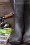 Aparejos de pesca y botas de goma en tablero de la madera Foto de archivo libre de regalías