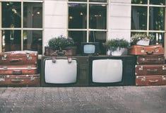 Aparelho de televisão do vintage dos lotes com as malas de viagem e as plantas retros velhas da casa em uns potenciômetros para a Imagem de Stock