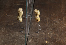 Apart. Couple of Peanut People being kept apart by a glass wall royalty free stock photo