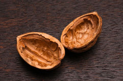 Apart walnut. Separated empty walnut shells with dark brown wooden background Stock Photography