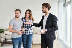 Apartamento de la casa de la demostración del agente inmobiliario o del propietario a los pares jovenes fotografía de archivo