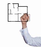 Apartamento del plan del dibujo del hombre de negocios de la mano Imágenes de archivo libres de regalías