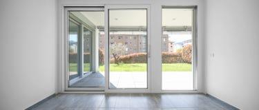 Apartamento moderno com as grandes, janelas brilhantes imagens de stock