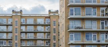 Apartamentos amarillos planos con la vivienda exterior de la arquitectura del balcón en la ciudad imágenes de archivo libres de regalías