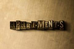 APARTAMENTOS - close-up vintage sujo da palavra typeset no contexto do metal Fotos de Stock Royalty Free