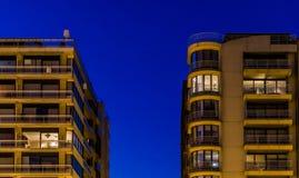 Apartamentos de la ciudad encendidos por la noche, arquitectura en Blankenberge, Bélgica foto de archivo