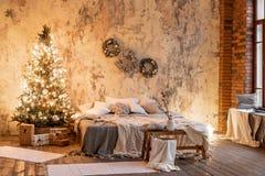 Apartamentos del desván, pared de ladrillo con las velas y la guirnalda del árbol de navidad Cama en el dormitorio, alto Windows  fotos de archivo