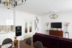 Apartamentos-estudios interiores con paredes blancas, una cocina y un sof Foto de archivo