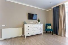 Apartamentos planos del desván interior del pasillo de Luxure con la cómoda de la silla y la TV foto de archivo libre de regalías