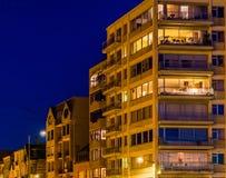 Apartamentos y edificios encendidos por noche, Blankenberge, Bélgica de la ciudad imagen de archivo