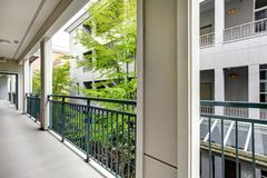 Apartment balcony with modern building court yard. Royalty Free Stock Image