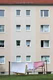 Apartment block. Clothesline with bedding in front of an apartment block Stock Photo
