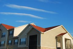 Apartment Building. Under warm sun, blue skies and interesting clouds Stock Photography