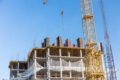 Apartment building construction site with crane against blue sky stock photos