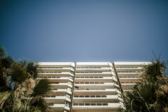 Apartment building facade between palm trees. Royalty Free Stock Images