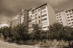 Apartment building and leafy trees on street. In a cloudy day at Covilha. Known as the town of wool and snow, stands at Estrela ridge proximity in eastern royalty free stock photo
