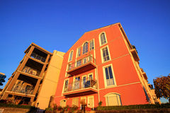 Apartment building with orange wall on blue sky at sunset Royalty Free Stock Images