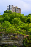 Apartment Building Overlooking Lush Trees. An urban apartment complex overlooks dense, lush, green trees and a rocky cliff royalty free stock photo