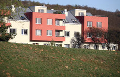 Apartment buildings. Coloured prefab houses with many windows hidden by the green field Stock Photography