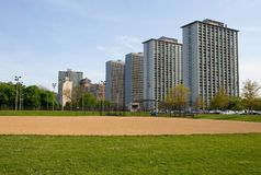Apartment buildings. Tall parallel apartment buildings and park with baseball field Royalty Free Stock Photos