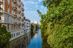Apartment buildings on bank of river or canal in residential district of Hamburg Eppendorf, Germany on sunny day. Apartment buildings on bank of river or canal stock photography