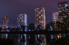 Apartment buildings with glowing windows near the pond at night. royalty free stock image