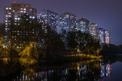 Apartment buildings with glowing windows near the pond at night. stock photos